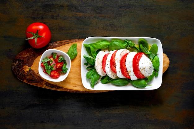 Antipasto de ensalada italiana llamado caprese con mozzarella de búfala, tomate y albahaca con aceite de oliva
