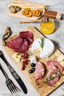 Antipasto italiano con jamón, salchichón, queso parmesano, brie y queso gorgonzola, miel.