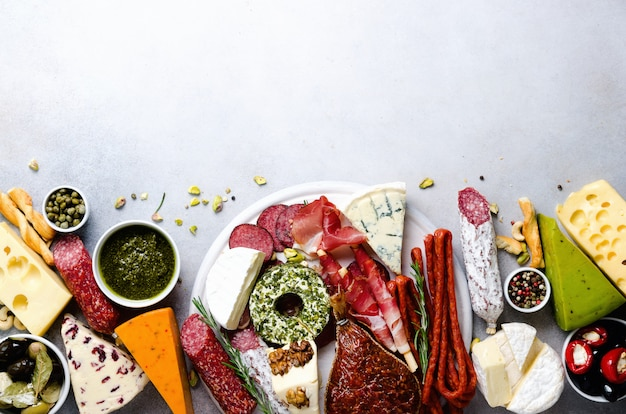 Antipasto italiano tradicional, tabla de cortar con salami, carne ahumada en frío, jamón, jamón, quesos, aceitunas, alcaparras en gris.