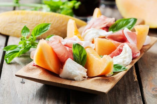 Antipasto con melón, mozzarella, jamón y albahaca