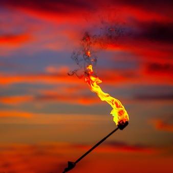Antorcha de fuego en el cielo del atardecer con nubes rojas