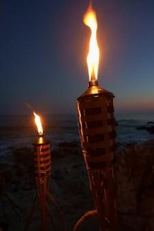 Antorchas de noche con llamas amarillas y reflejos.