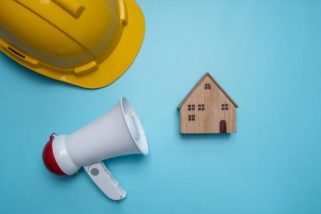 Anuncio y anuncio de antecedentes publicitarios de relaciones públicas sobre construcción de edificios, viviendas, viviendas y bienes inmuebles con megáfono y casco amarillo.