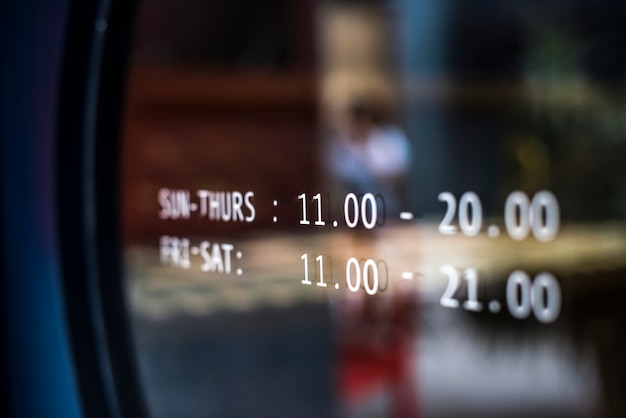 Anuncio de horario comercial en una ventana