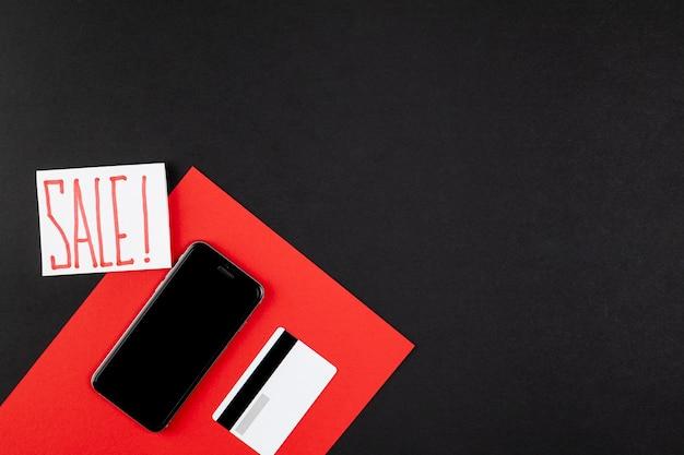 Anuncio de venta junto a tarjeta de crédito y maqueta de teléfono