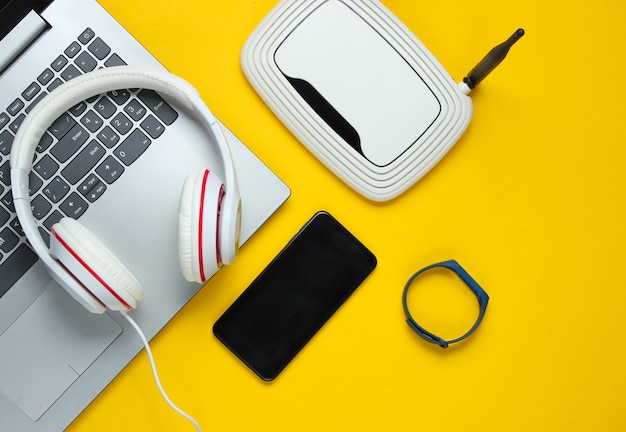 Aparatos y accesorios digitales modernos. ordenador portátil, smartphone, pulsera inteligente, auriculares, enrutador wi-fi sobre un fondo amarillo.