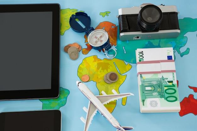 Aparatos electrónicos, cámara, dólar, brújula y modelo de avión.