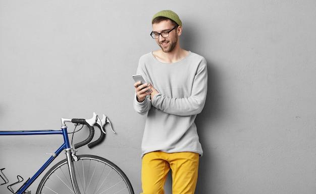 Aparatos modernos, tecnologías y concepto de comunicación en línea. apuesto chico feliz con rastrojo relajante después de andar en bicicleta, usando messenger en el teléfono celular para comunicarse con amigos en línea