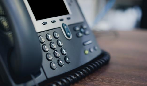 Aparatos telefónicos en el escritorio de la oficina