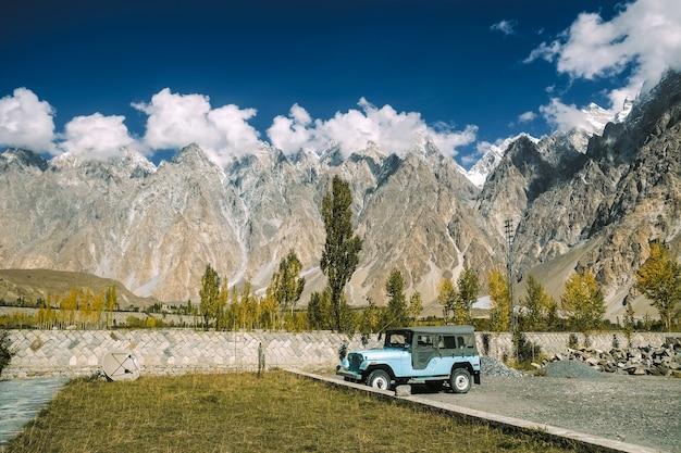 Un aparcamiento azul cerca de los picos de montaña de los conos de passu con la opinión del otoño.