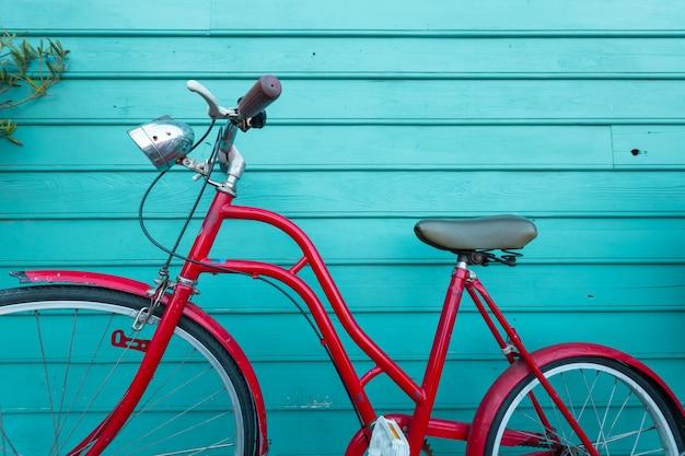 Aparcamiento bicyle rojo vintage en pared de madera azul