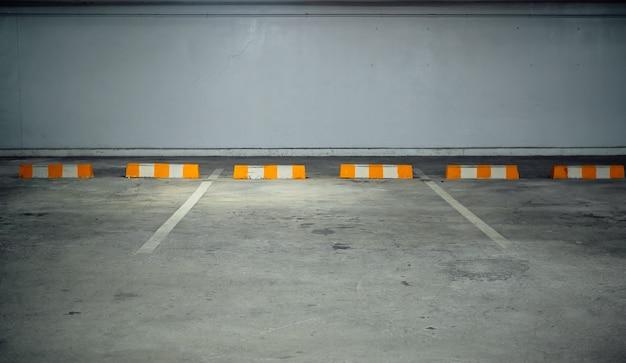 Aparcamiento gratuito en el edificio con barreras blancas amarillas.
