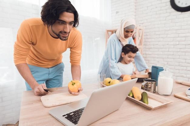 Apariencia árabe en ropa moderna en cocina con laptop.