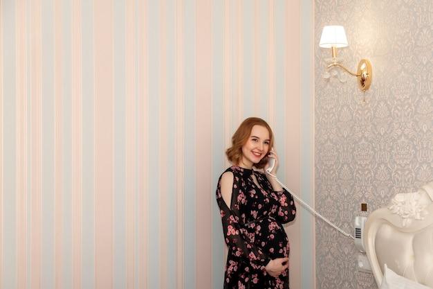 La apariencia eslava de la mujer joven embarazada en el vestido está de pie contra la pared con el auricular del teléfono en la habitación del hotel.