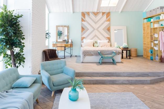 Apartamento espacioso de moda con un diseño elegante en colores pastel verde, gris y blanco con ventana grande y paredes decorativas. espacio de dormitorio y cocina