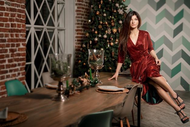 En un apartamento de lujo, sentada en una silla en un apartamento de lujo, una magnífica joven con un lujoso vestido rojo y preciosas joyas.
