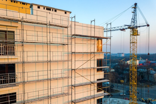 Apartamento u oficina alto edificio sin terminar en construcción. pared de ladrillo en andamios, ventanas brillantes y grúa torre en paisaje urbano y cielo azul. drone fotografía aérea.