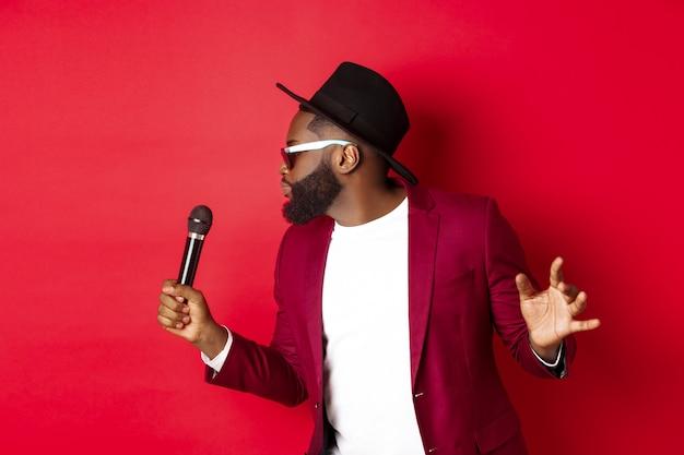 Apasionado cantante masculino negro actuando sobre fondo rojo, cantando en el micrófono, vistiendo traje de fiesta, de pie sobre fondo rojo.