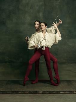 Apasionado. dos jóvenes bailarinas de ballet como duelistas con espadas en la pared verde oscuro. modelos caucásicos bailando juntos. concepto de ballet y coreografía contemporánea.