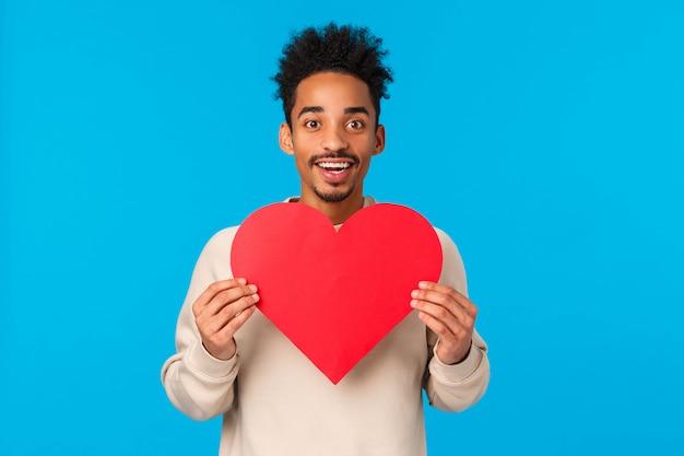 Apasionado y emocionado chico afroamericano enamorado dando su corazón al alma gemela, buscando la otra mitad, sosteniendo el corazón valentines cad y sonriendo como expresar afecto, azul