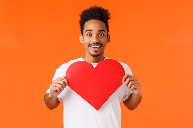 Apasionado y feliz novio afroamericano enamorado, felicitando a la mujer el día de san valentín, mostrando la tarjeta del corazón y sonriendo, expresando afecto, pidiendo ser su novia, buscando alma gemela
