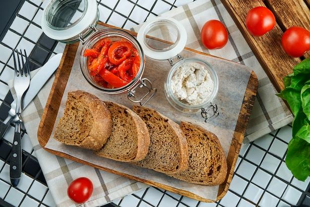 Aperitivo antes del plato principal. pimientos en vinagre con queso crema y tostadas de centeno sobre papel artesanal. vista superior. comida plana