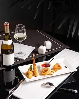 Aperitivo con aros de cebolla y gambas servido con salsa y vino