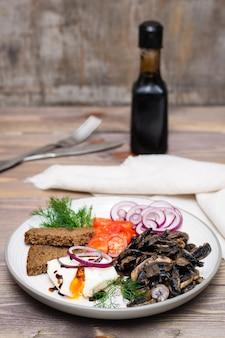 Aperitivo de champiñones, cebollas, tomates y huevos escalfados en un plato sobre una mesa de madera