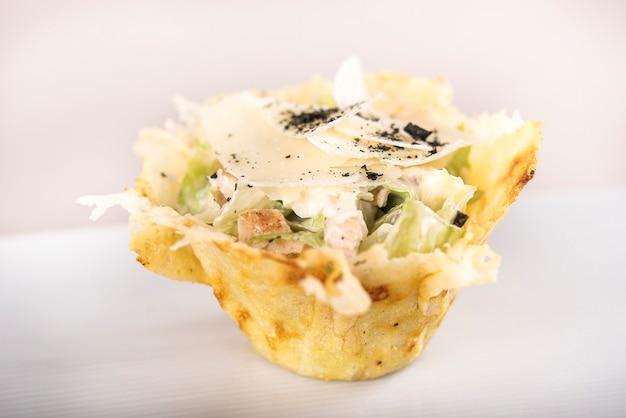 Aperitivo con ensalada caeser y filete de pollo, servido en una canasta de parmesano, plato blanco