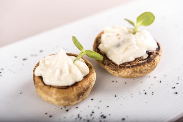 Aperitivo fresco con champiñones, relleno de mayonesa, decorado con hojas verdes.