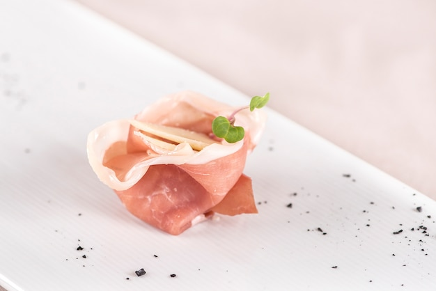Aperitivo fresco con jamón prosciutto y rodajas de queso parmesano, decorado con hojas verdes.