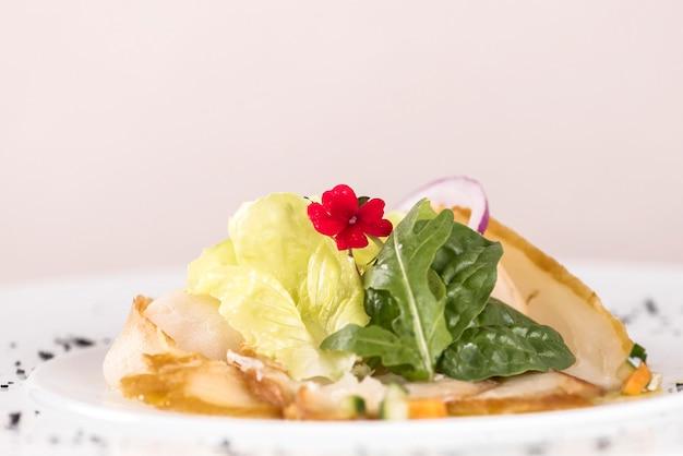 Aperitivo fresco con pescado blanco ahumado, rúcula, espinaca y ensalada verde, con flores rojas