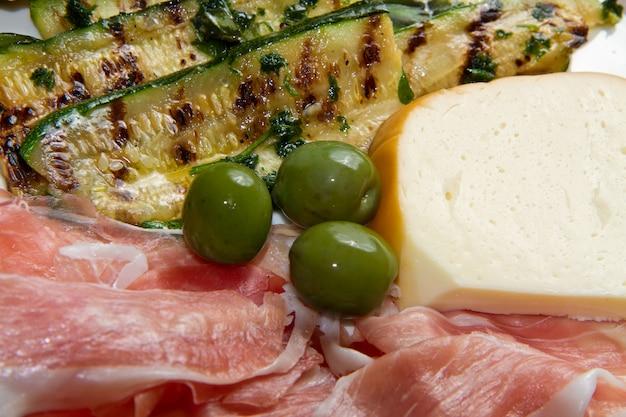 Aperitivo con jamón crudo, queso y verduras a la plancha.