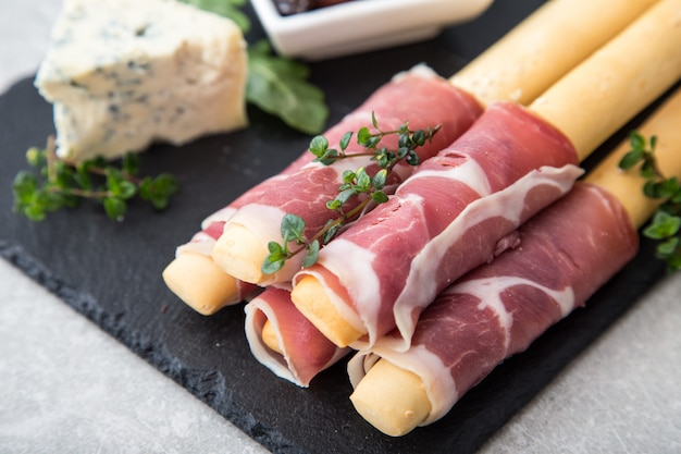 Aperitivo con jamón, jamón, queso azul y tomates secos para las fiestas.