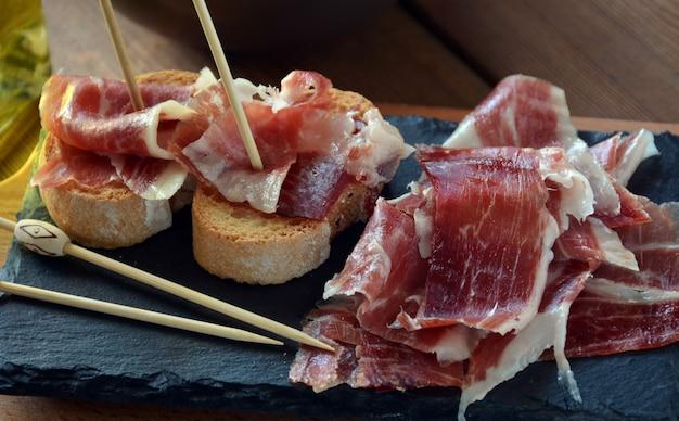 Aperitivo de jamón serrano con pan asado y acompañado de una copa de vino.