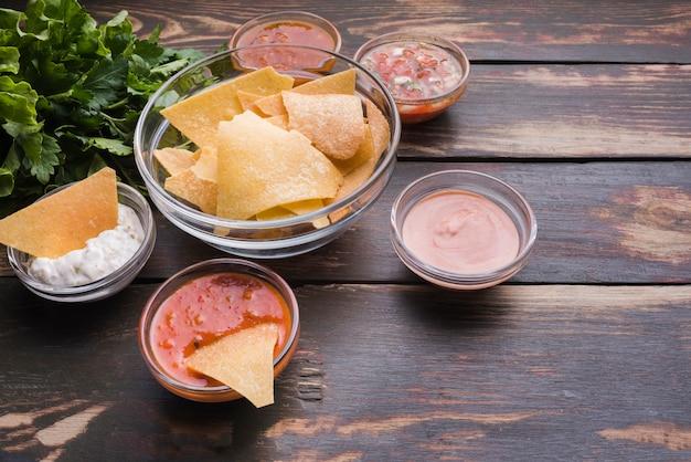 Aperitivo de nachos con salsas en mesa.