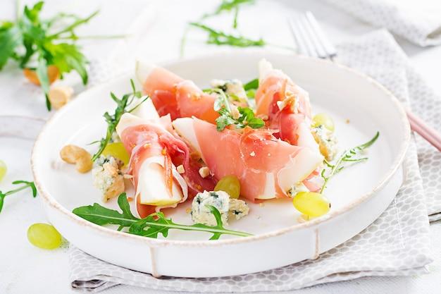 Aperitivo con pera, queso azul y jamón prosciutto para vacaciones en un plato blanco.