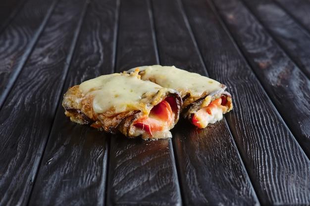 Aperitivo para la recepción. berenjenas rellenas de tocino, jamón, cebolla y queso derretido