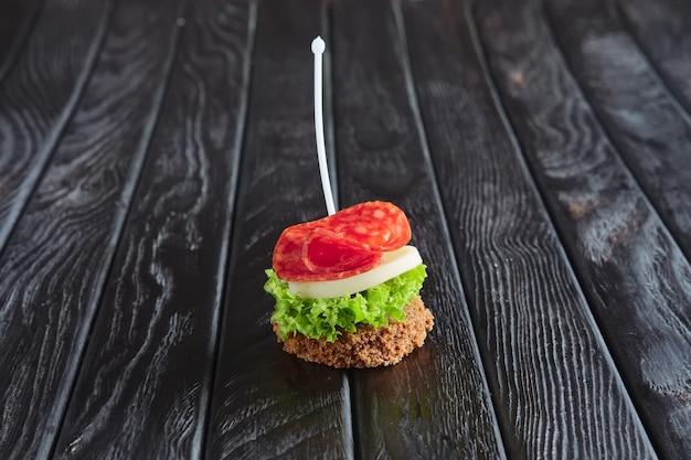 Aperitivo para la recepción. sándwich pequeño con salchicha, sheese y ensalada de hojas en brocheta