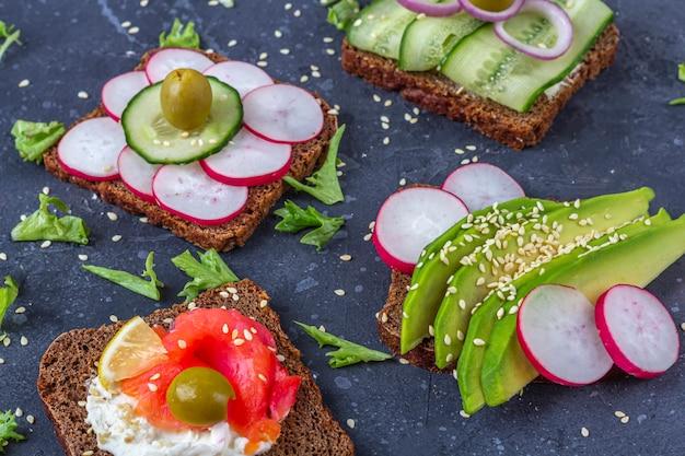 Aperitivo, sándwich abierto con diferentes ingredientes: salmón y verduras (aguacate, pepino, rábano) sobre una superficie oscura. alimentación saludable. comida orgánica y vegetariana. cerrar, copiar espacio para texto