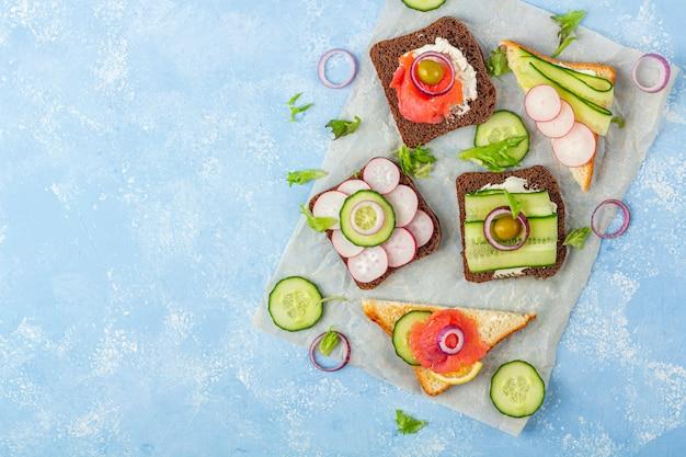 Aperitivo, sándwich abierto con diferentes ingredientes: salmón y verduras en un papel sobre fondo azul. merienda tradicional italiana o escandinava. alimentación saludable. cerrar, copiar espacio para texto