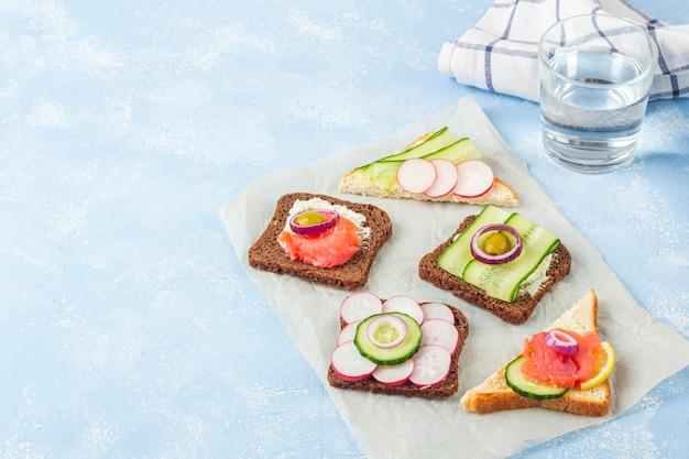 Aperitivo, sándwich abierto con diferentes ingredientes: salmón y verduras en un papel sobre fondo azul. merienda tradicional italiana o escandinava. alimentación saludable