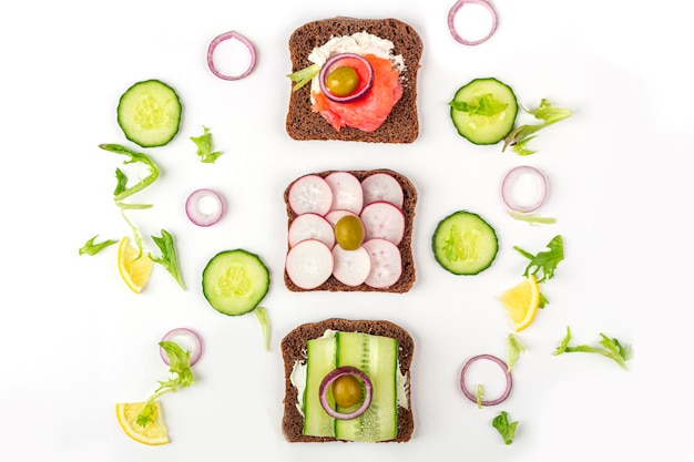 Aperitivo, sándwich abierto con diferentes ingredientes: salmón y verduras sobre fondo blanco. cocina tradicional italiana o escandinava. alimentación saludable