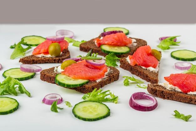 Aperitivo, sándwich abierto con salmón, cebolla y pepino sobre fondo blanco. cocina tradicional italiana o escandinava. concepto de nutrición adecuada y alimentación saludable. de cerca