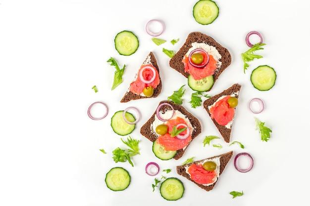 Aperitivo, sándwich abierto con salmón, cebolla y pepino sobre fondo blanco. cocina tradicional italiana o escandinava. concepto de nutrición adecuada y alimentación saludable.