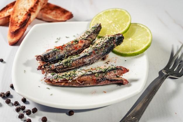 Aperitivo de sardinas en aceite con perejil y pimentón en un plato con tostadas y rodajas de limón. vista alta.