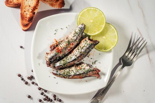 Aperitivo de sardinas en aceite con perejil y pimentón en un plato con tostadas y rodajas de limón. vista superior.