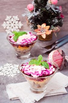 Aperitivo tradicional ruso de verduras y pescado hervido, un arenque bajo un abrigo de piel en cuencos con adornos navideños en la mesa. ensalada rusa