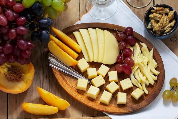 Un aperitivo de varios tipos de quesos, uvas y nueces, servido con vino. estilo rústico.