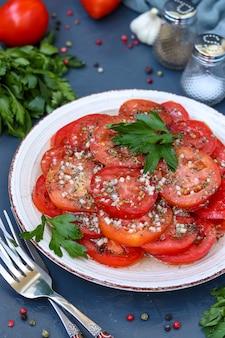 Aperitivo vegetariano de tomates con ajo, perejil, aderezado con miel y aceite de oliva ubicado en un plato